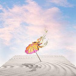 Flaming cocktail umbrella on wind swept sand with sky background