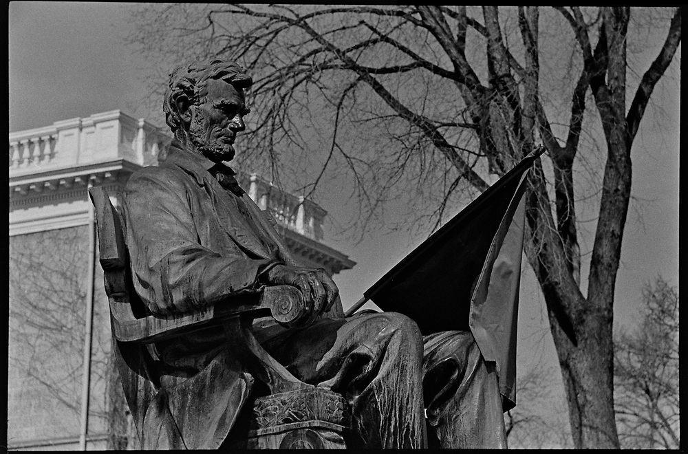 Madison, WI - March 1970. The statue of Abraham Lincoln in front of Bascom Hall, with a black and red anarcho-syndicalism flag. On March 15, 1970, the University of Wisconsin - Madison Teaching Assistants' Association voted to strike, and the campus was filled with picket lines as well as demonstrations of related and other issues. The strike lasted until early April, when the Association and University came to an agreement.