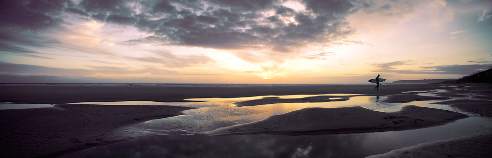 Panoramic of surfer at sunset walking up the beach in St Ouen, Jersey, CI with orange light reflecting in the pools of water in the sand.