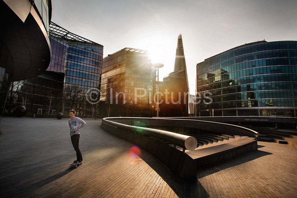 Skateboarder keeping fit during the lockdown by City Hall at 5pm on 9th April 2020 in London, United Kingdom. Normally crowded with people leaving work the City of London is like a ghost town as workers stay home during the Coronavirus pandemic.