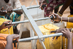 30 May 2019, Mokolo, Cameroon: Women wait for their jerry cans to fill up at one of the tapstands in Minawao camp. The Minawao camp for Nigerian refugees, located in the Far North region of Cameroon, hosts some 58,000 refugees from North East Nigeria. The refugees are supported by the Lutheran World Federation, together with a range of partners.