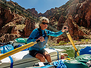 Arizona Raft Adventures (AZRA) trip leader Lorna Corson rows under Bright Angel Bridge (aka Silver Bridge). Built in the late 1960s, the Silver Bridge supports hikers and the Transcanyon Water Distribution Pipeline across the Colorado River, connecting the Bright Angel Trail from the South Rim to Phantom Ranch and the North Rim. Hikers only (no mules) may cross this narrow suspension bridge. Five-hundred-thousand gallons of water a day are piped from Roaring Springs near the North Rim down Bright Angel Canyon through Phantom Ranch, across the Colorado River, and then pumped up to provide almost all the water to the South Rim tourist area. Day 6 of 16 days rafting 226 miles down the Colorado River in Grand Canyon National Park, Arizona, USA. For this photo's licensing options, please inquire at PhotoSeek.com. .