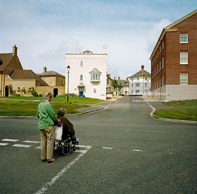 Seen from behind as they stop at dotted give-way lines on this empty road junction, we see a strange perspective of deserted housing and empty roads, Jen West and her elderly wheelchair-bound mother Margaret - both residents of the experimental community village of Poundbury, Dorset, England. As if they are pedestrians about cross a busy highway, it is an incongruous scene of irony. Poundbury is the visionary model village that Charles, Prince of Wales sought to develop in 1993 as a successful and pioneering town near Dorchester, built on land owned by his own Duchy of Cornwall, challenging otherwise poor post-war trends in town planning and to some extent following the New Urbanism concept from the US except that the design influences are European.