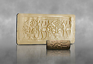 Hittite cylinder seal depicting a scene of animals, seal in foreground and impression standing behind.. Adana Archaeology Museum, Turkey. Against a grey art background .<br /> <br /> If you prefer to buy from our ALAMY STOCK LIBRARY page at https://www.alamy.com/portfolio/paul-williams-funkystock/hittite-art-antiquities.html . Type - Adana - in LOWER SEARCH WITHIN GALLERY box. Refine search by adding background colour, place, museum etc<br /> <br /> Visit our HITTITE PHOTO COLLECTIONS for more photos to download or buy as wall art prints https://funkystock.photoshelter.com/gallery-collection/The-Hittites-Art-Artefacts-Antiquities-Historic-Sites-Pictures-Images-of/C0000NUBSMhSc3Oo