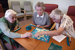 Group of elderly women playing game of scrabble at day centre,