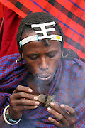 Africa, Tanzania, Young Maasai man with head ornament lights a fire with cow dung an ethnic group of semi-nomadic people