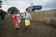 A couple of festival goers making their way in the mud, drinks in hand, at Glastonbury Festival 25th July 2016, Somerset, United Kingdom.  The Glastonbury Festival runs over 3 days and has 3000 acts, including music, art and performance and approx. 150.000 attend the anual event.