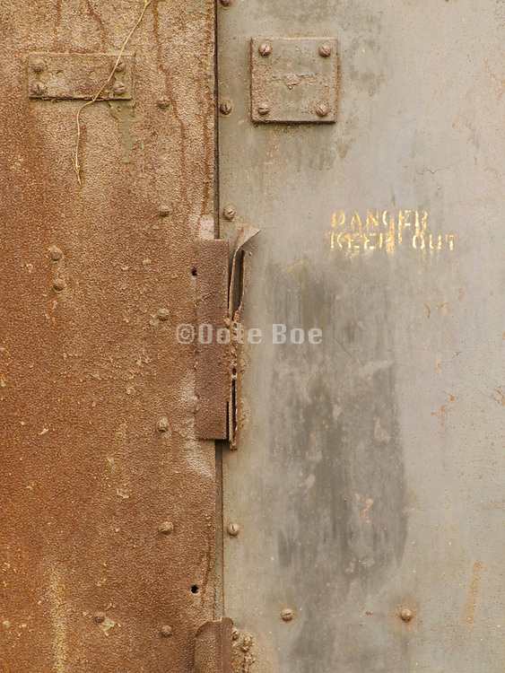 Close up of an old metal door welded shut with text danger keep out.