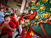 """19 FEBRUARY 2015 - BANGKOK, THAILAND: A woman reacts to a Chinese dragon dancer passing her in a restaurant on Chinese New Year in Bangkok. 2015 is the Year of Goat in the Chinese zodiac. The Goat is the eighth sign in Chinese astrology and """"8"""" is considered to be a lucky number. It symbolizes wisdom, fortune and prosperity. Ethnic Chinese make up nearly 15% of the Thai population. Chinese New Year (also called Tet or Lunar New Year) is widely celebrated in Thailand, especially in urban areas that have large Chinese populations.    PHOTO BY JACK KURTZ"""