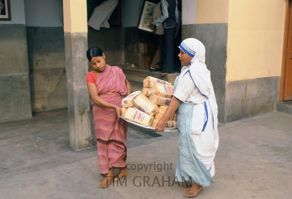 Nun and helper carrying loaves of bread to give to women collecting food aid at Mother Teresa's Mission for the Poor in Calcutta, India