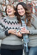 Mother and Daughter laughing with  hot cider in their hands during a winter holiday family photography session in Dedham, Massachusetts around Thanksgiving in November of 2018.