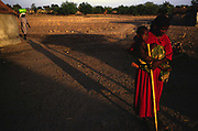 Asumpaheme, who is blind, goes to collect water at a water hole. Her grandchild is strapped to her back. She is blind due to the entirely preventable 'River Blindness' (Onchocerciasis) Despite herhandicap, she has no choice but to continue farming.