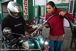 A Nepalese woman pumps gas for Jonathan Pite on day-4 of our Himalayan Heroes adventure as we rode from Pokhara to Kalopani, Nepal. Friday, November 9, 2018. Photography ©2018 Michael Lichter.