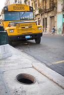 Schoolbus and open manhole, Havana, Cuba