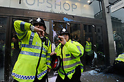 Police in riot gear protecting Topshop on Oxford Street as Anti capitalists / anarchists go on the rampage on the back of the peaceful TUC protest march on 26th March 2011 in London, United Kingdom. The masked demonstrators ran a twisting route through the capital confusing the police and creating a situation which was very difficult to manage. The protesters attacked banks, shops and hotels, and the police in riot gear fought  face to face with them as they were pelted with ammonia, paint and fireworks loaded with coins.