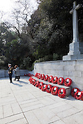 A man in naval uniform inspects poppy wreaths after a Remembrance Day ceremony at the Yokohama War Cemetery, Hodogaya. Yokohama, Japan. Sunday November 9th 2014
