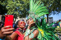 © Licensed to London News Pictures. 26/08/2019. London, UK. A member of public takes a selfie with a dance on the second day of Notting Hill Carnival in west London. Thousands of revellers take part in Notting Hill Carnival, Europe's largest street party and a celebration of Caribbean traditions and the capital's cultural diversity. Photo credit: Dinendra Haria/LNP