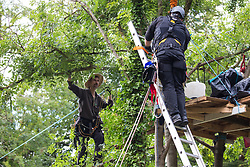 Denham, UK. 24 July, 2020. Larch (l), an environmental activist from HS2 Rebellion, negotiates terms with a police officer (r) to come down from a line above the river Colne attached to an ancient alder tree which he was trying to protect from destruction in connection with works for the HS2 high-speed rail link in Denham Country Park. A large policing operation involving the Metropolitan Police, Thames Valley Police, City of London Police and Hampshire Police as well as the National Eviction Team was put in place to enable HS2 to destroy the tree.