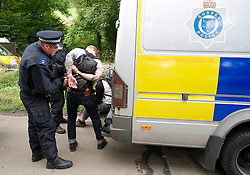 © London News Pictures. 19/08/2013. Balcombe, UK. A man being arrested by police as activists clash with police outside to the Cuadrilla drilling site in Balcombe, West Sussex on a day of of civil disobedience organised by campaign group No Dash For Gas. Cuadrilla has temporarily ceased drilling at the site, which has been earmarked for fracking, under advice from the police. Photo credit: Ben Cawthra/LNP