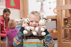 Portrait of grinning little boy with two soft toys in kindergarten