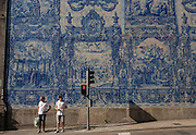 Two young wait to cross the road beneath traditional Azulejo tiles on the wall of Capela Das Almas (church), on Rua Santa Catarina Porto, Portugal. The panels depict scenes from the lives of various saints including the death of St Francis and the martyrdom of St Catherine. Eduardo Leite painted the tiles in a classic 18th-century style, though they actually date back only to the early 20th century.