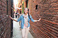 Young women are amazed at the narrow corridor of Fan Tan Alley, an area in Chinatown that features interesting shops in downtown Victoria, BC.