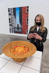 """© Licensed to London News Pictures. 13/05/2021. LONDON, UK.  London, UK.  13 May 2021. A staff member views """"Maze Meal"""", 2019, by Julie Curtiss.  Preview of """"Monads and Dyads"""", the first London exhibition by New York-based artist Julie Curtiss.  Her surrealist works feature new paintings, works on paper and sculptures.  The show is at White Cube Mason's Yard in Mayfair 14 May to 26 June 2021.  Photo credit: Stephen Chung/LNP"""
