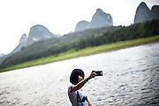 A Chinese girl takes a selfie on the River Li in YangShuo, Guilin, August 1, 2014.<br /> <br /> Smartphones are an essential tool of Chinese ordinary life. Everywhere in China, people use them to take pictures to share online, to talk and chat, to play videogames, to get access to the mainstream information, to get connected one each other. In the country where the main global social media are forbidden - Facebook, Twitter and Youtube are not available  -, local social networks such as WeChat have a wide spread all over the citizens. The effect is an ordinary and apparently compulsive way to get easy access to digital technology and modern way of communication. <br /> A life through the display. Yes, We Chat.<br /> <br /> © Giorgio Perottino