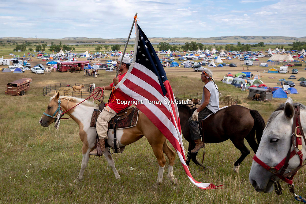 Christopher Dion (left) and Ken Fourcloud, both of the Crow Creek Sioux Reservation, ride through the resistance encampment against the Dakota Access oil pipeline on September 8, 2016, near Cannon Ball, North Dakota. Dion carried a replica of the flag carried by U.S. cavalry soldiers before their defeat by the Sioux at the 1876 Battle of the Little Bighorn, or as it's more commonly called among the victors, the Battle of the Greasy Grass.