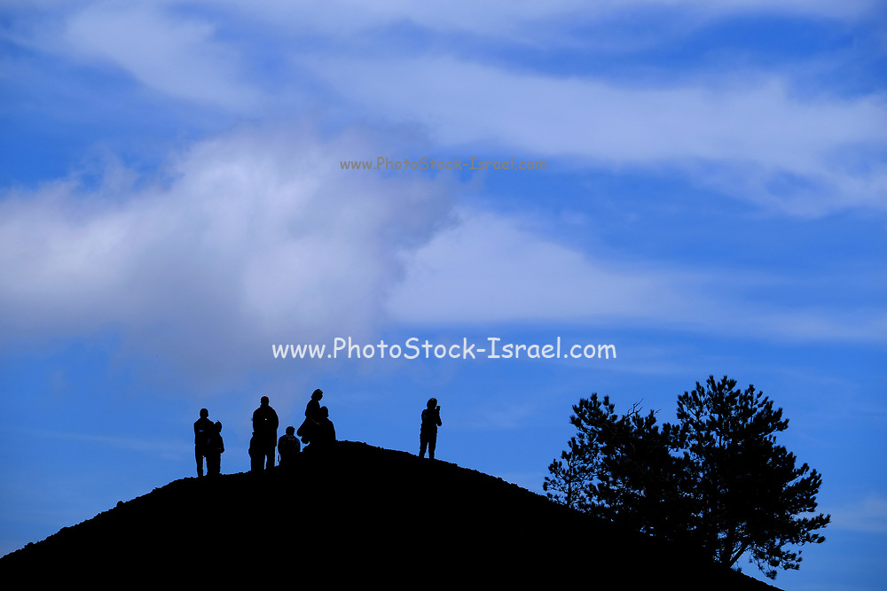 people silhouetted on a blue sky background at the summit of Mount Etna, Sicily, Italy