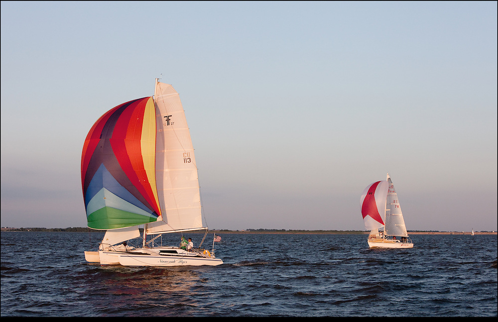Colorful mainsails in Cheney Lake near sunset.