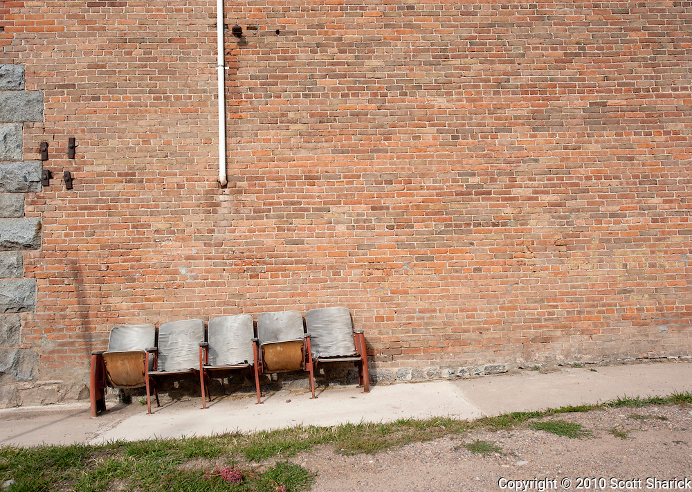 A row of old theater seats sits out along a brick wall in Phillipsburg, Montana. Missoula Photographer, Missoula Photographers, Montana Pictures, Montana Photos, Photos of Montana