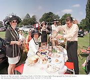 Note from Dafydd: This one was used on the cover of a magazine. The calls came in from readers.- The man pouring champage has 3 hands. It is true. He does. - Funny that no-one on the picture desk noticed. <br /> I like the feeling of movement it gives. <br /> Picnic in the car-park. Tote Ebor.York. 19/8/98. © Copyright Photograph by Dafydd Jones<br /> 66 Stockwell Park Rd. London SW9 0DA<br /> Tel 0171 733 0108