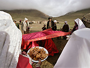 "The bride, along with her sisters and other close female relatives are squatting under a red cloth in front of the ceremonial yurt while the men around the cloth are throwing candies on the cloth and distributing ""bortsok"" (fried dough), to bring good luck to the wedding. Meanwhile, the girls are weeping and crying, signifying the upcoming ""loss"" of the bride to her husdand's family.<br /> The Kyrgyz wedding ceremony of Koormoochoo Saïra (son of Yunus Amid) in Utch Djelgha summer camp, 5th August 20005.<br /> <br /> Adventure through the Afghan Pamir mountains, among the Afghan Kyrgyz and into Pakistan's Karakoram mountains. July/August 2005. Afghanistan / Pakistan."