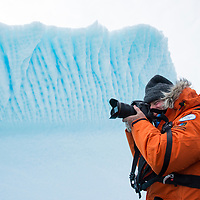 A man photographs from an inflatable boat in front of a beautifully sculpted iceberg in Port Charcot near Booth Island, Antarctica.