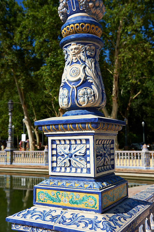 Tiled  lamp column of the Plaza de Espana in Seville built in 1928 for the Ibero-American Exposition of 1929, Seville Spain . The Royal Alcázars of Seville (al-Qasr al-Muriq ) or Alcázar of Seville, is a royal palace in Seville, Spain. It was built by Castilian Christians on the site of an Abbadid Muslim alcazar, or residential fortress.The fortress was destroyed after the Christian conquest of Seville The palace is a preeminent example of Mudéjar architecture in the Iberian Peninsula but features Gothic, Renaissance and Romanesque design elements from previous stages of construction. The upper storeys of the Alcázar are still occupied by the royal family when they are in Seville. <br /> <br /> Visit our SPAIN HISTORIC PLACES PHOTO COLLECTIONS for more photos to download or buy as wall art prints https://funkystock.photoshelter.com/gallery-collection/Pictures-Images-of-Spain-Spanish-Historical-Archaeology-Sites-Museum-Antiquities/C0000EUVhLC3Nbgw <br /> .<br /> Visit our MEDIEVAL PHOTO COLLECTIONS for more   photos  to download or buy as prints https://funkystock.photoshelter.com/gallery-collection/Medieval-Middle-Ages-Historic-Places-Arcaeological-Sites-Pictures-Images-of/C0000B5ZA54_WD0s