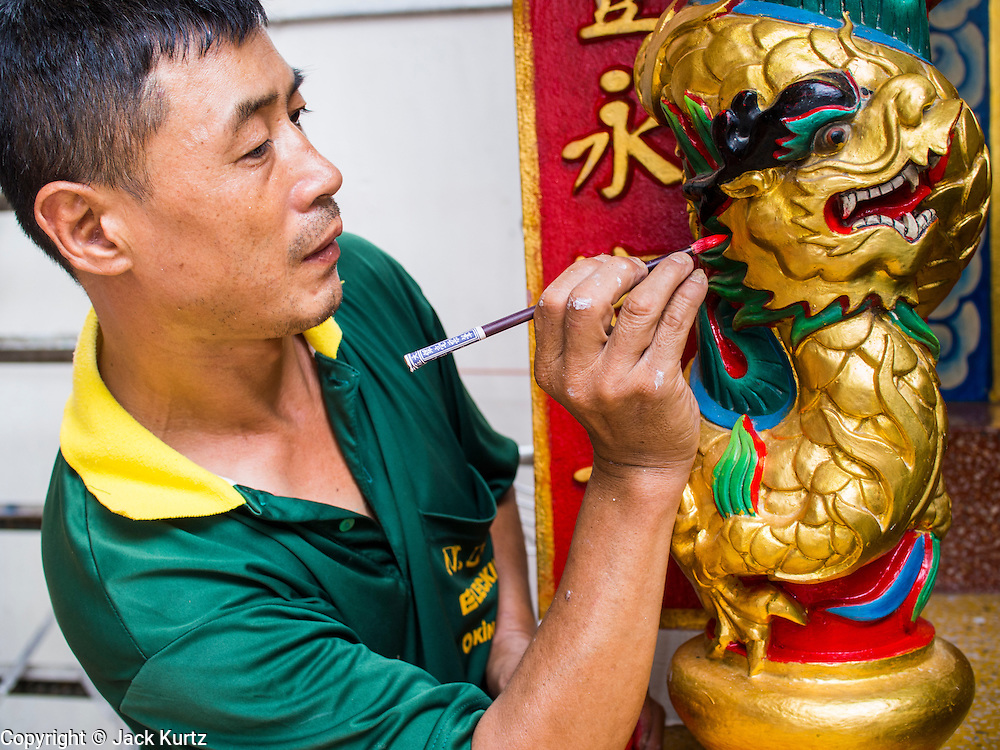 14 AUGUST 2014 - BANGKOK, THAILAND:     A man paints a dragon in a small Chinese shrine in the Talat Noi section of Bangkok. Most Thais are Theravada Buddhists but many Chinese-Thais are Mahayana Buddhists. Talat Noi is a small part of Chinatown that dates back to the Ayutthaya period. It is a melting pot of various cultures and was originally settled by Portuguese,  Vietnamese, Hokkien, Teochew and Hakka Chinese. Now it is mostly small mechanical shops and used car parts.   PHOTO BY JACK KURTZ