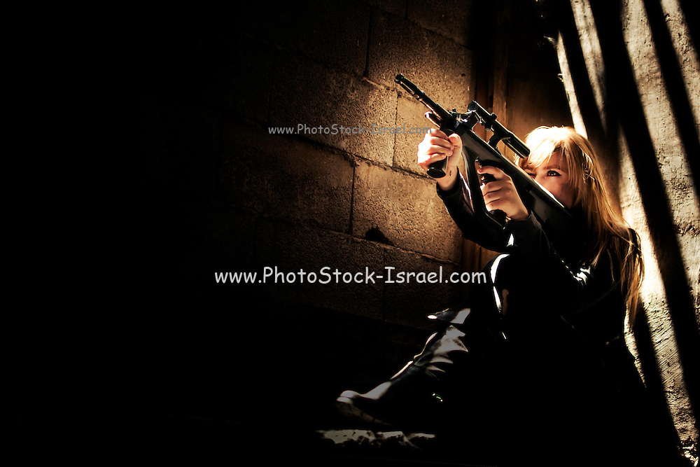 Aggressive Young woman in her 20s with automatic rifle