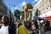 Man carrying a wooden cross as if Jesus on Ladbroke Grove on Monday 28th August 2016 at the 50th Notting Hill Carnival in West London. A celebration of West Indian / Caribbean culture and Europes largest street party, festival and parade. Revellers come in their hundreds of thousands to have fun, dance, drink and let go in the brilliant atmosphere. It is led by members of the West Indian / Caribbean community, particularly the Trinidadian and Tobagonian British population, many of whom have lived in the area since the 1950s. The carnival has attracted up to 2 million people in the past and centres around a parade of floats, dancers and sound systems.