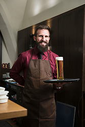 Portrait of smiling manager carrying large glass of beer on tray