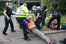 Godstone, UK. 13th September, 2021. Police officers arrest a Insulate Britain climate activist who had blocked a slip road from the M25 as part of a new campaign intended to push the UK government to make significant legislative change to start lowering emissions. The activists, who wrote to Prime Minister Boris Johnson on 13th August, are demanding that the government immediately promises both to fully fund and ensure the insulation of all social housing in Britain by 2025 and to produce within four months a legally binding national plan to fully fund and ensure the full low-energy and low-carbon whole-house retrofit, with no externalised costs, of all homes in Britain by 2030 as part of a just transition to full decarbonisation of all parts of society and the economy.