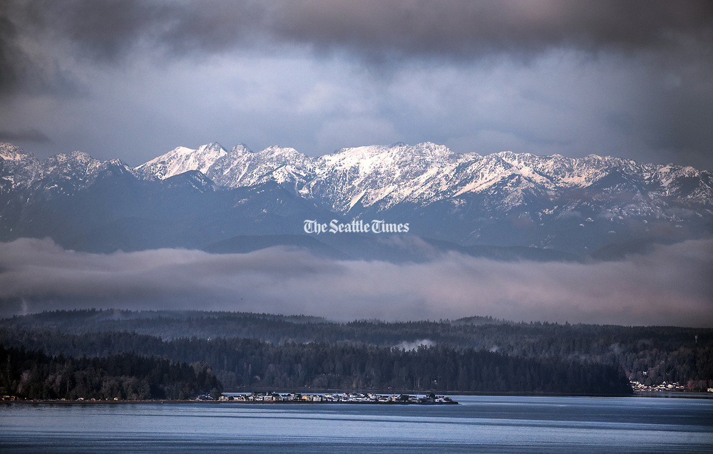Looking across the Puget Sound to the first snowfall to blanket the upper reaches of the Olympics.  Bainbridge Island and Point Monroe are in the forground. (Steve Ringman / The Seattle Times)