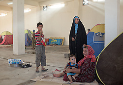 © Licensed to London News Pictures. 25/06/2014. Khanaqin, Iraq. Iraqi refugees are seen amongst tents in a barn at the refugee camp on the outskirts of Bahari Taza village in Iraq. Located on the outskirts of Khanaqin, a town just 20 minutes from the front-line of the battle with ISIS insurgents, the Bahari Taza refugee camp, and its satellite camps, now house around 600 families from southern Iraq. Built by the local village leader to meet the influx of refugees from nearby Jalawla and Saidia, where intense fighting is still taking place. Turkman, Arab and Kurd, both Sunni and Shia, all live together in tents, barns and unfinished buildings waiting for the conflict to end. Photo credit: Matt Cetti-Roberts/LNP