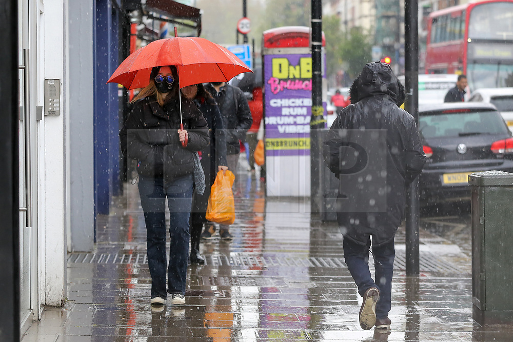 © Licensed to London News Pictures. 02/05/2021. London, UK. A woman shelters from heavy rain beneath an umbrella in north London. Windy and wet weather is forecasted for the bank holiday Monday. Photo credit: Dinendra Haria/LNP