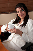 Young woman relaxes in the office having a cup of coffee.