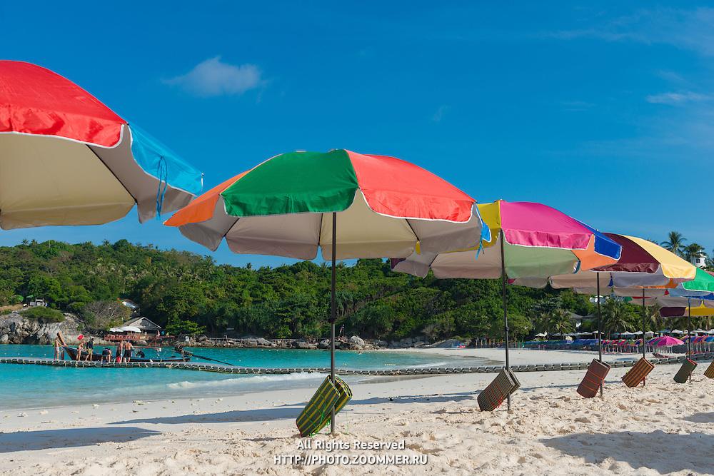 Beach umbrellas waiting for tourists in Raya island, Thailand