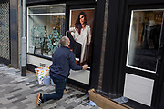 A workman fixes and adjusts a poster of a female model outside a high street fashion business 'The White Company', on 7th November 2019, in Kingston, London, England