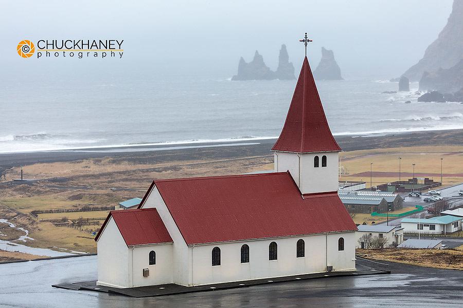Vik i Myrda church lines up with Reynisdrangar sea stacks with in Vik, Iceland