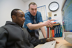 Young man in a computer training session with teacher,