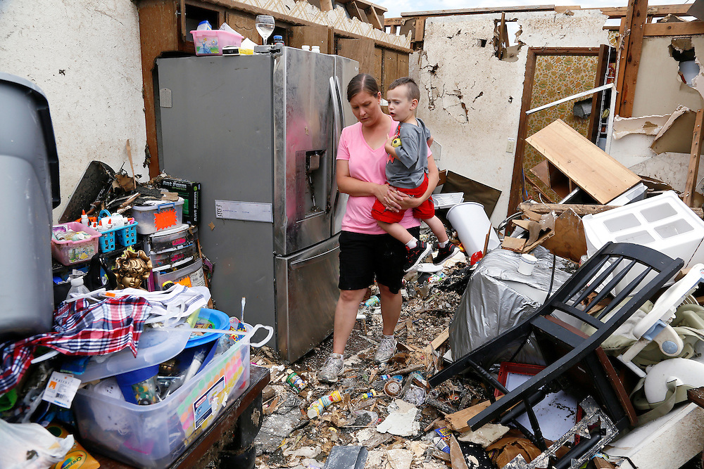 Tracy Stephan holding her son Timothy, 3, looks at her tornado-destroyed home on 6th Avenue in Moore, Oklahoma May 23, 2013. The tornado was the strongest in the United States in nearly two years and cut a path of destruction 17 miles long and 1.3 miles wide. REUTERS/Rick Wilking (UNITED STATES)